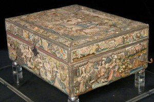 A stumpwork casket worked by Hannah Trapham in 1671. The wooden casket is covered with embroidered panels worked on ivory-coloured silk satin. The five main embroidered panels depict several religious and court scenes and are worked in silks, chenille, metallic thread and pearls, and they are trimmed with silver gilt braids; the narrow panels forming the sides of the lid contain embroidered flowers, insects and animals. The interior is lined with madder-dyed silk, quilted in parts. The casket stands on four silver ball feet and has a fretted silver hasp and lock engraved 'Hannah Trapham 1671'. Little is know about who Hannah Trapham was, although it is believed that the family came from Wingham in Canterbury, Kent.